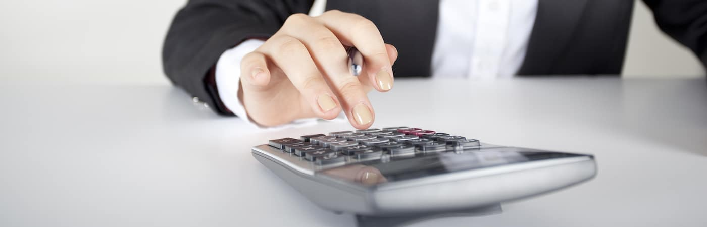 hand typing into calculator