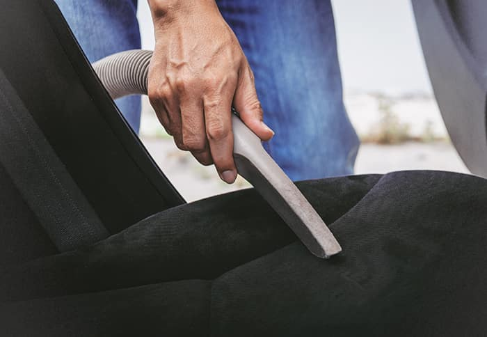 Where do I begin the process of trading in a vehicle at Boch Automotive of Massachusetts | Man Vacuuming car seat