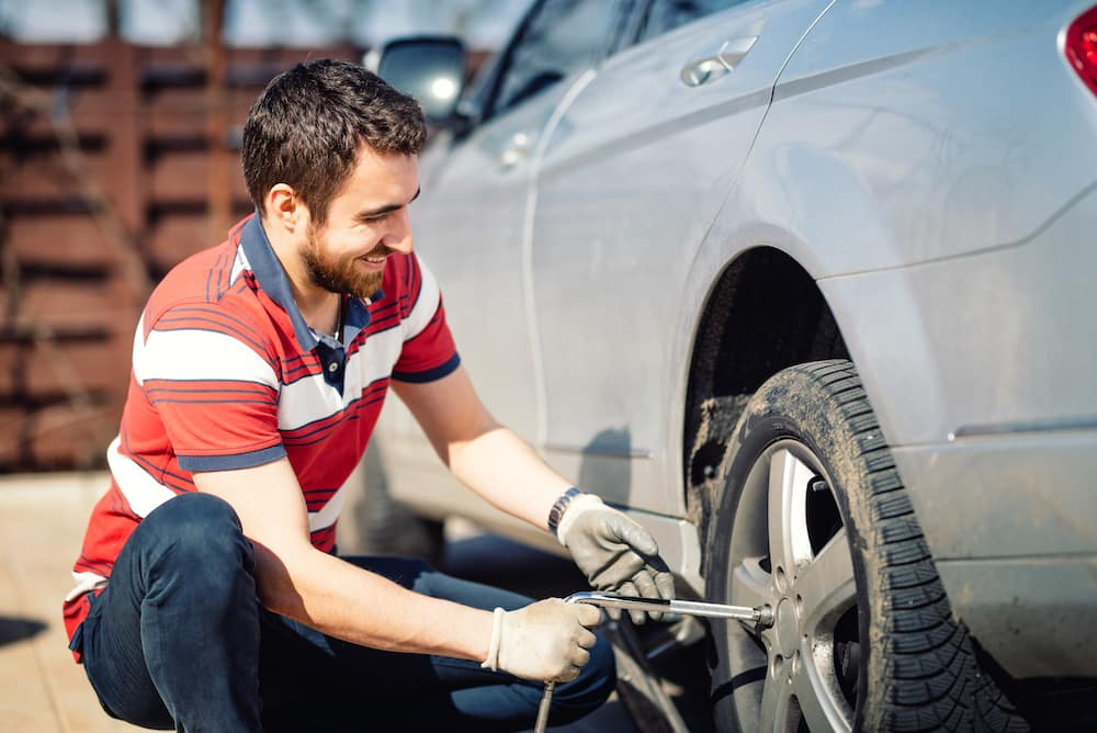 How to change a tire step-by-step guide at Boch Honda in Norwood | Man changing car tire