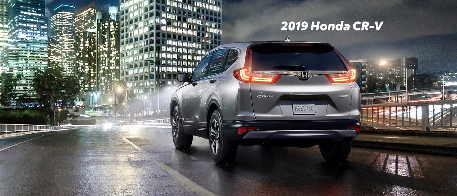 Comparison of the 2019 Pilot versus 2019 CR-V at Boch Honda of Norwood | Sliver 2019 Honda CR-V parked on street at night