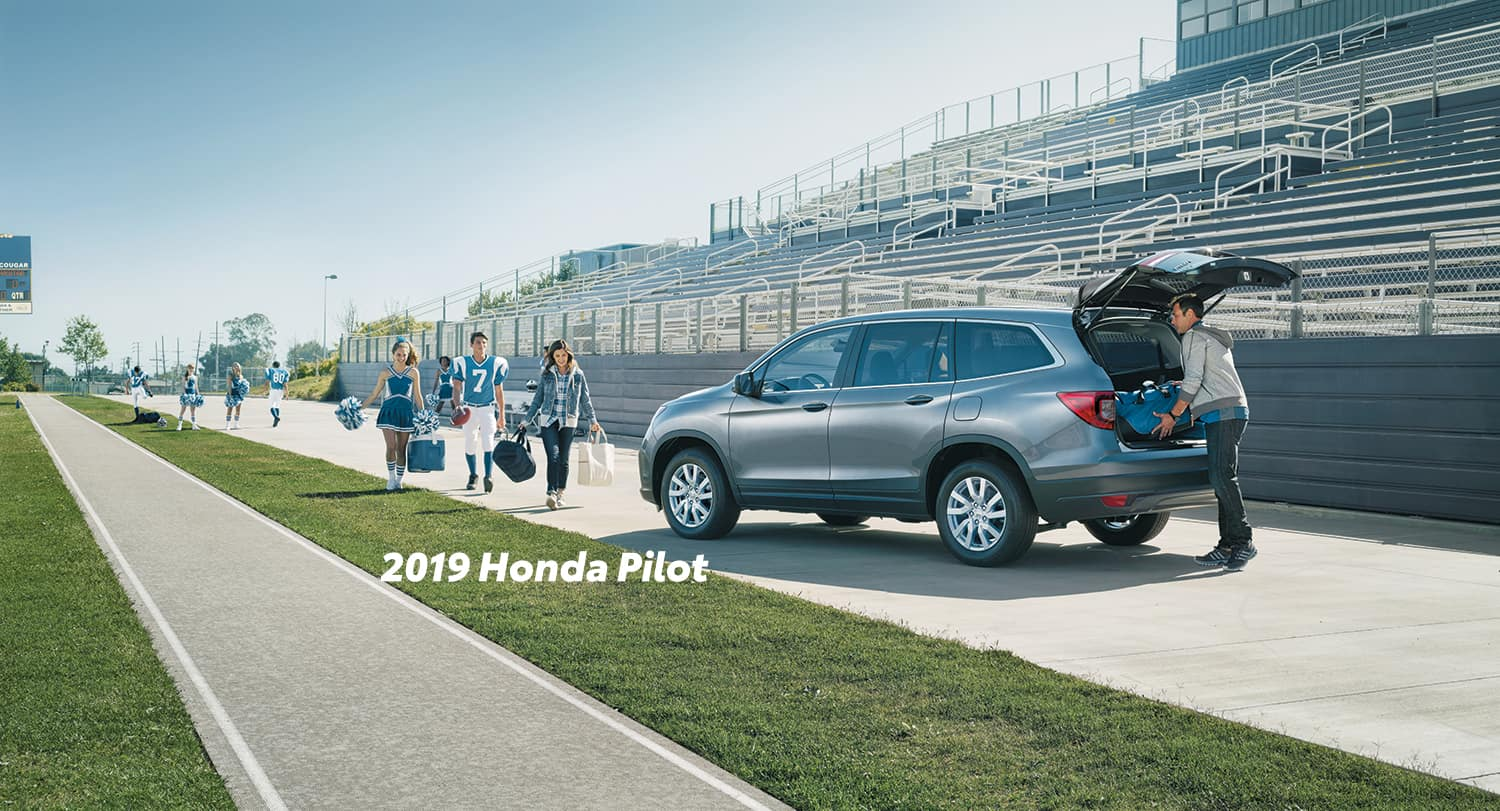 Comparison of the 2019 Pilot versus 2019 CR-V at Boch Honda of Norwood | 2019 Honda Pilot parked infront of a football field