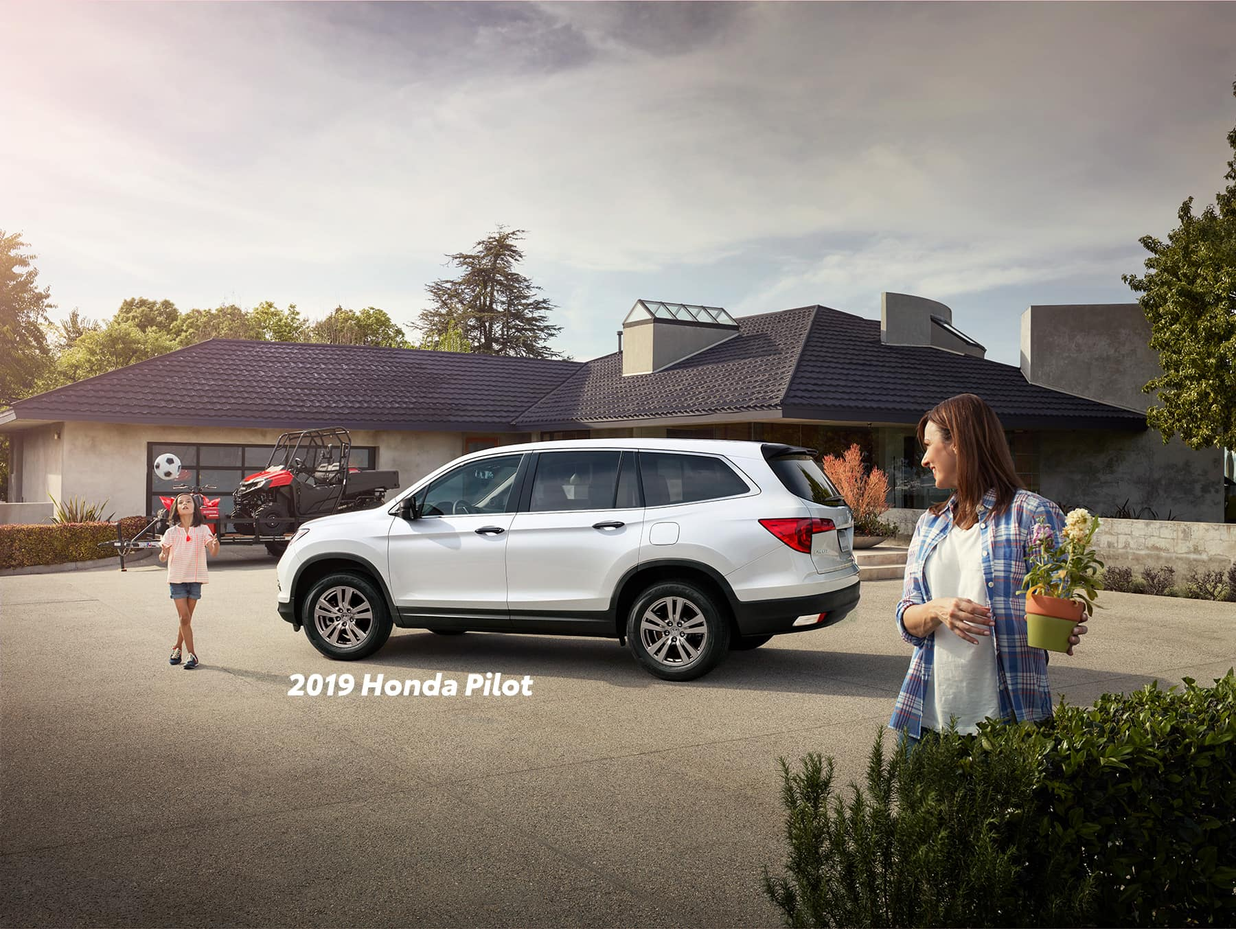Comparison of the 2019 Pilot versus 2019 CR-V at Boch Honda of Norwood | White 2019 Honda Pilot parked infron of a house