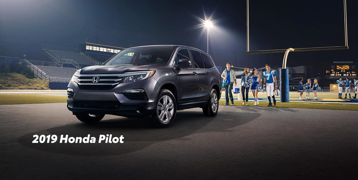 Comparison of the 2019 Pilot versus 2019 CR-V at Boch Honda of Norwood | 2019 Honda Pilot parked infront of football field