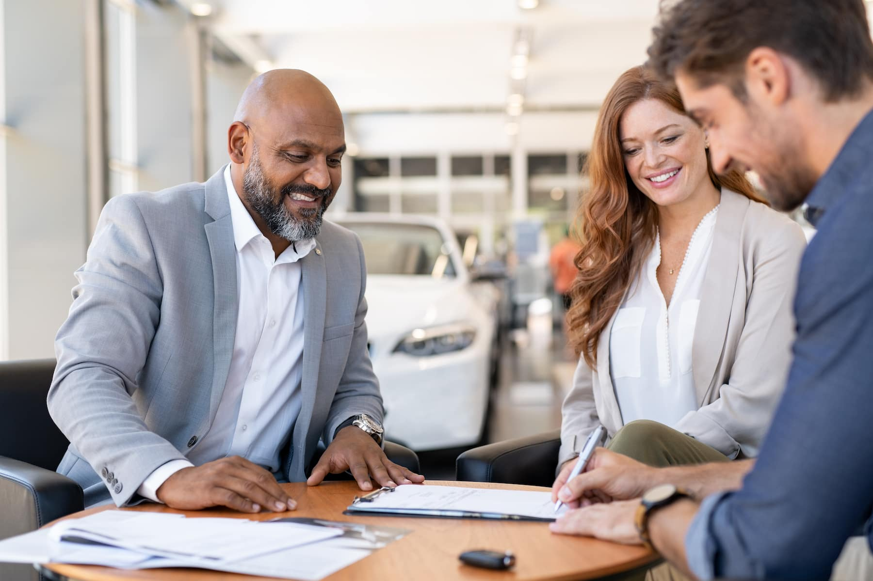 Documents to purchase a car at Boch Nissan in Norwood | Man signing documentation