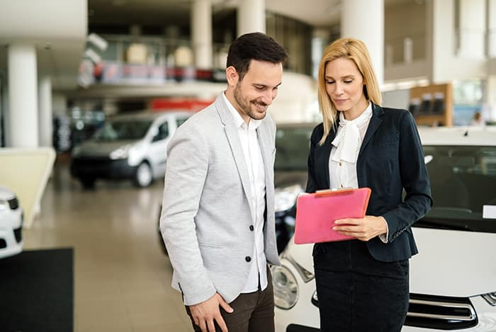 Documents to purchase a car at Boch Nissan in Norwood | Sales agent showing man documentation