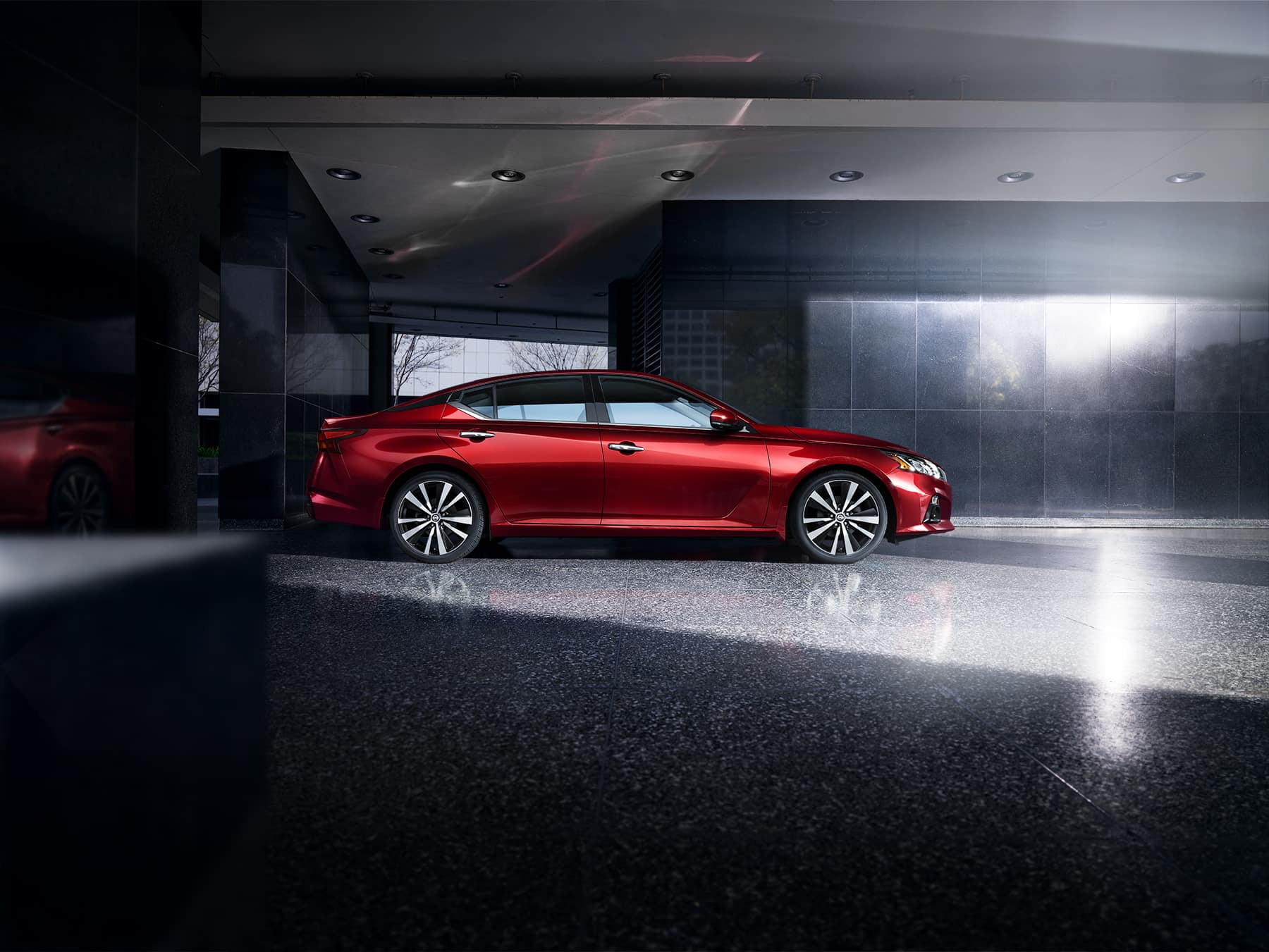 Model Features of the 2020 Nissan Altima at Boch Nissan of Norwood | red nissan altima park inside a building