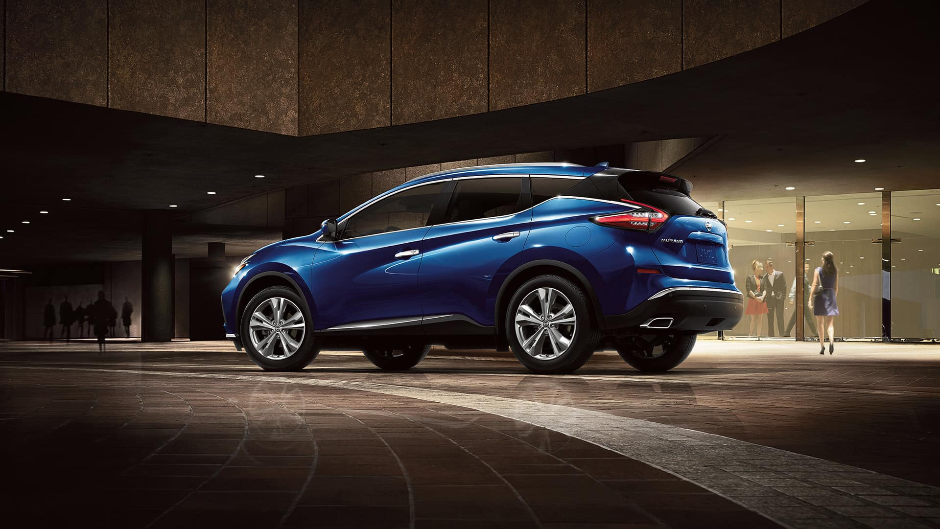 Nissan Boston is a Car Dealership near Boston MD | Blue MY20 Nissan Murano parked in front of dim lit luxury store front
