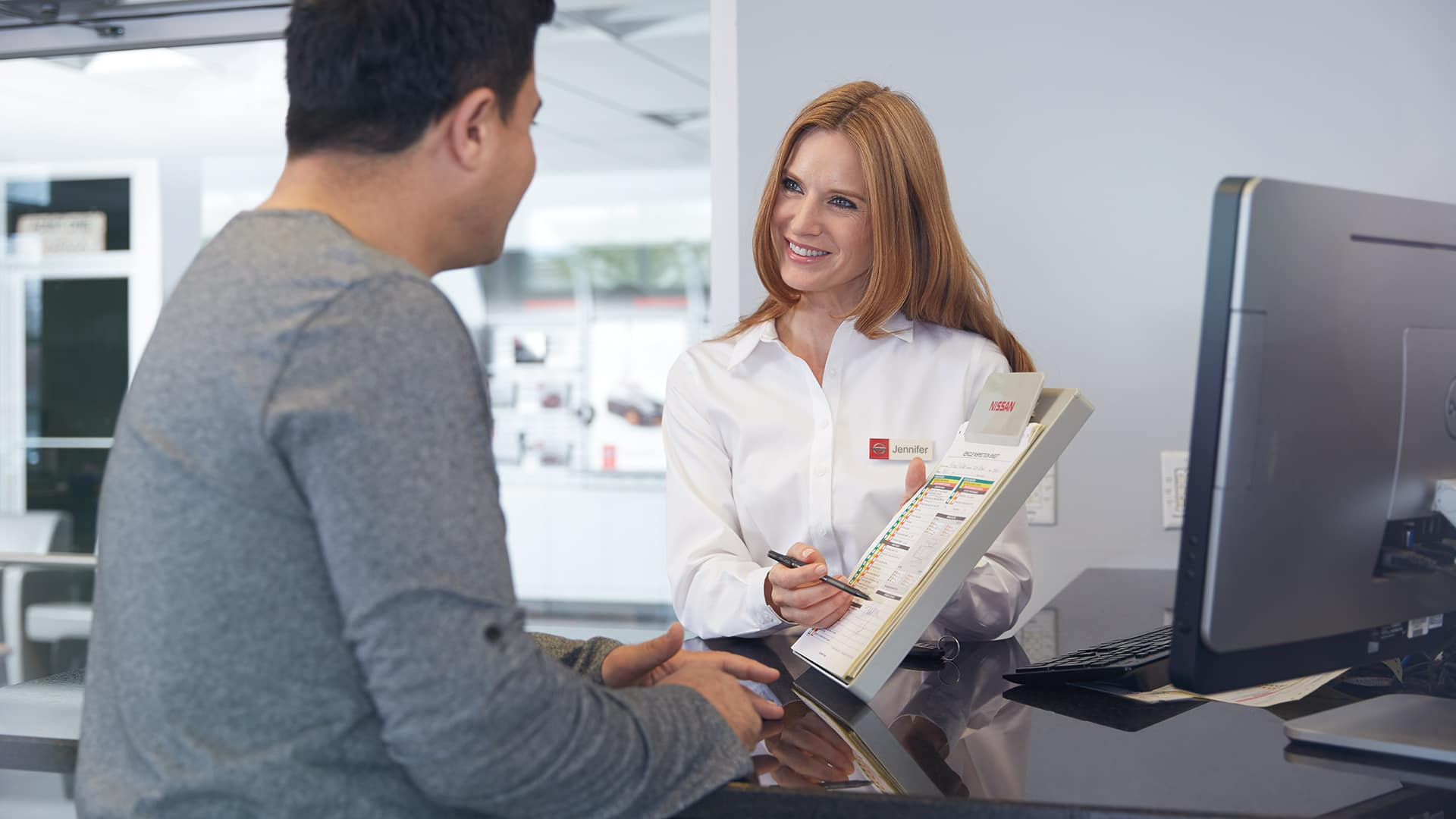 Nissan Boston is a Car Dealership near Boston MD | Nissan advisor showing a customer pricing options