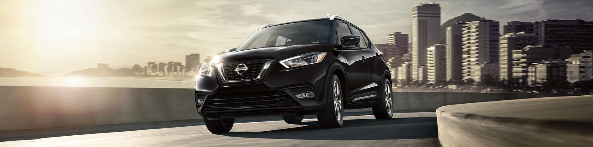Nissan Boston is a Car Dealership near Boston MD | Black MY19 Nissan Kicks driving on highway with city in background