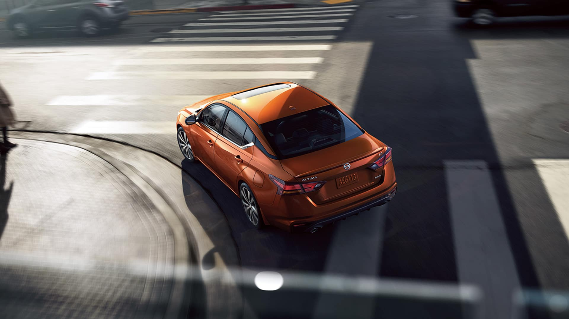 Boch Nissan is a Family Owned Dealership near Stoughton, MA | Orange MY20 Nissan Altima turning on city intersection