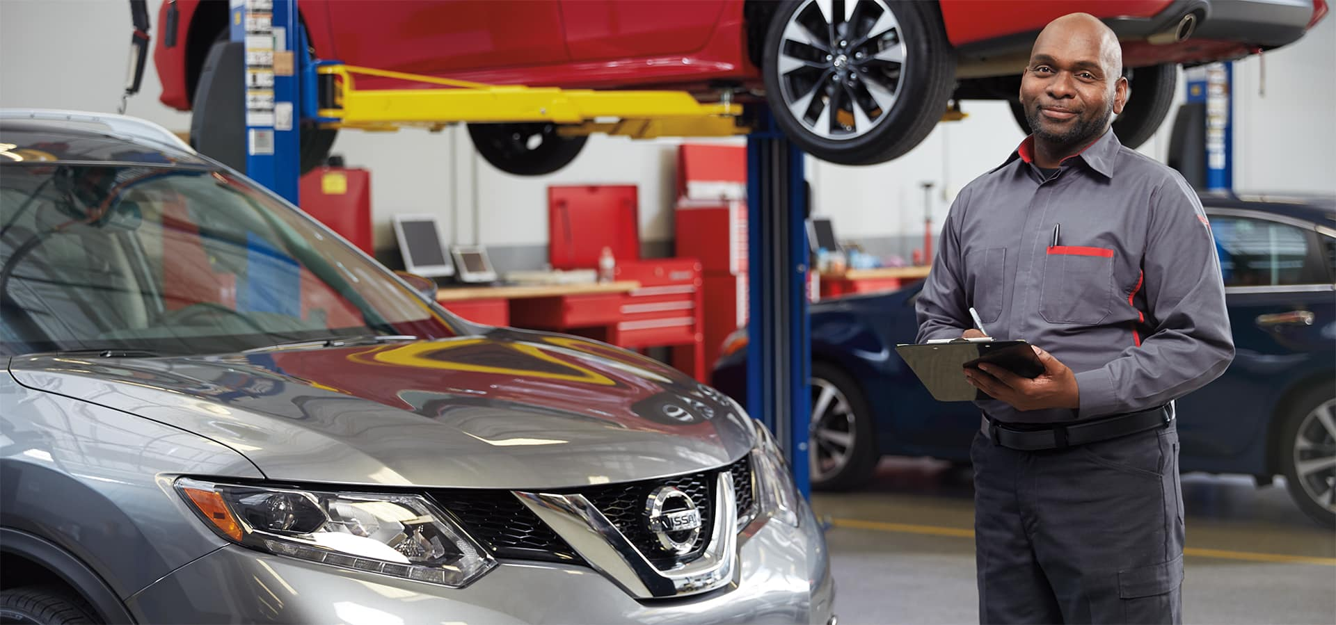 Boch Nissan is a Nissan Dealer Near Walpole MA | Nissan Service Advisor Standing Next to Nissan SUV