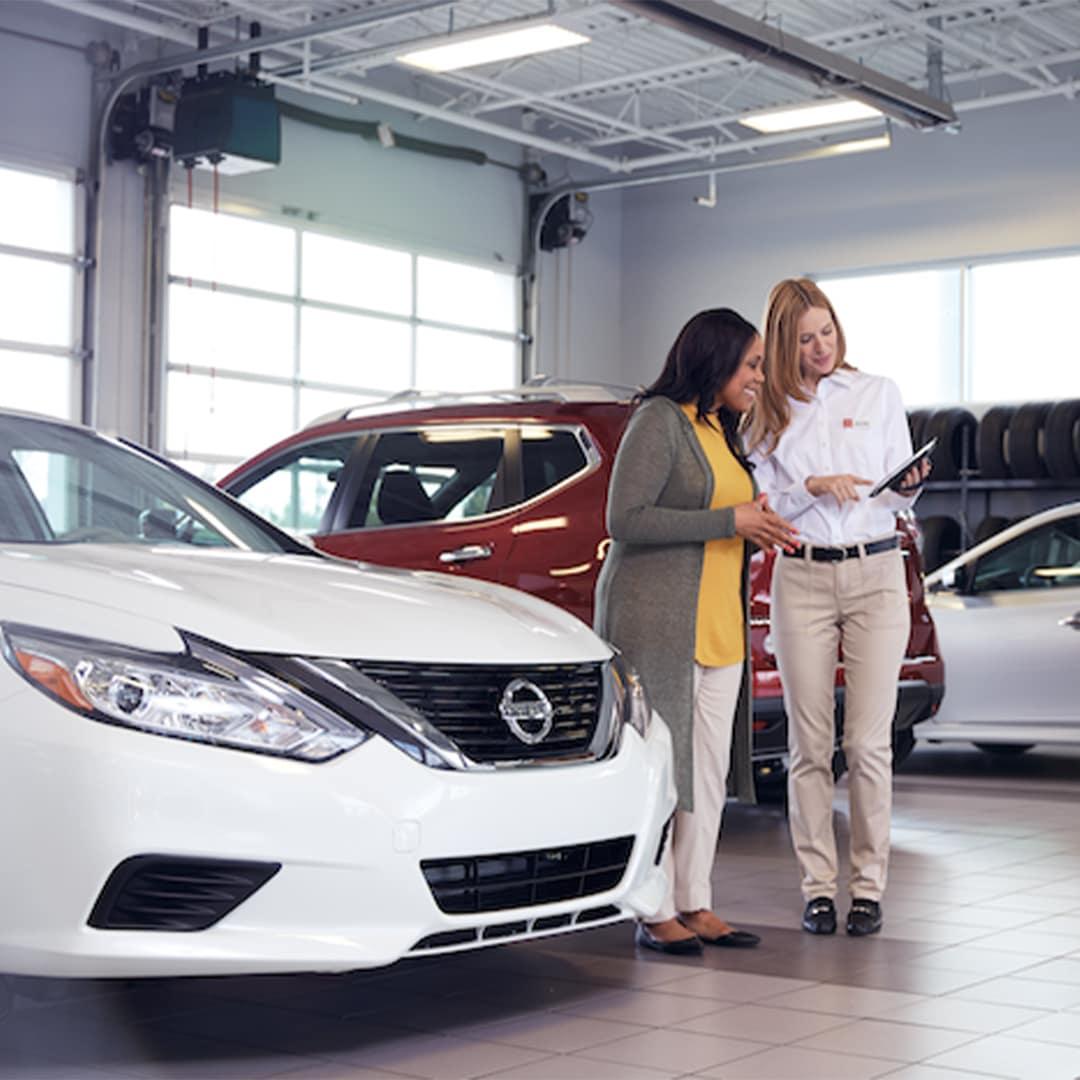 Boch Nissan is a Nissan Dealer Near Walpole MA | Nissan Advisor Talking with Customer While Standing Next to White Nissan Sedan