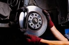 Technician changing brake and rotors on a vehicle
