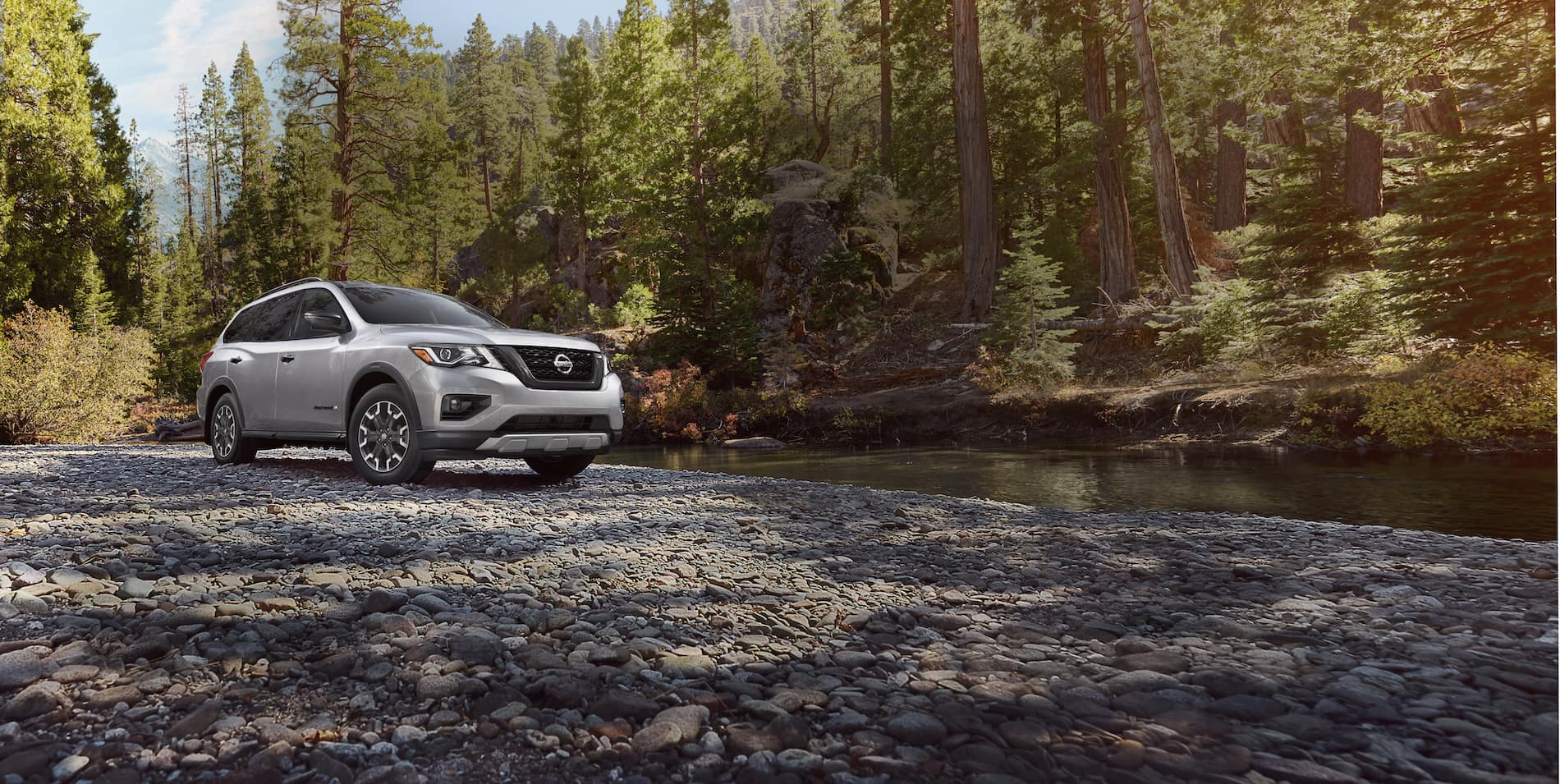 The features and trim levels of the 2019 Nissan Pathfinder | Grey 2019 Nissan Pathfinder parking near the river