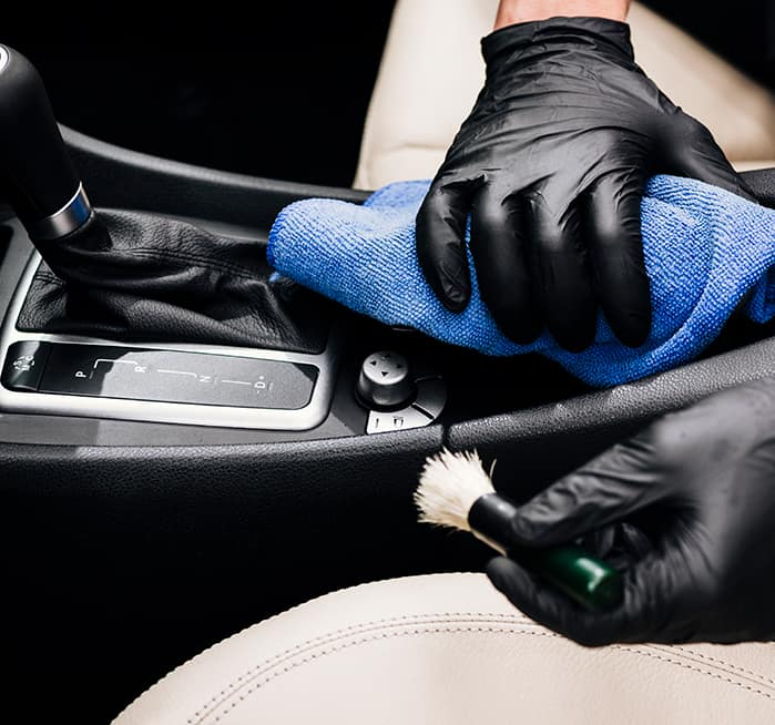 Where do I begin the process of trading in a vehicle at Boch Nissan South of North Attleboro | Man deatiling the interior of a car
