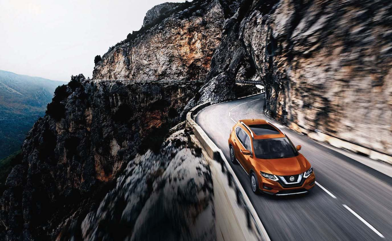 The 2020 Rogue model features at Boch Nissan South in North Attleboro | white 2020 rogue driving up the mountain