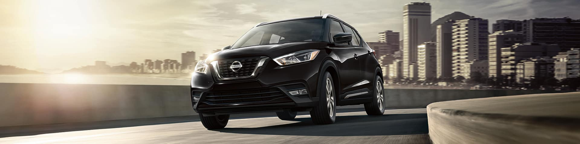Boch Nissan South is a Family Owned Dealership near Cumberland, RI | Black MY19 Nissan Kicks driving on highway outside city