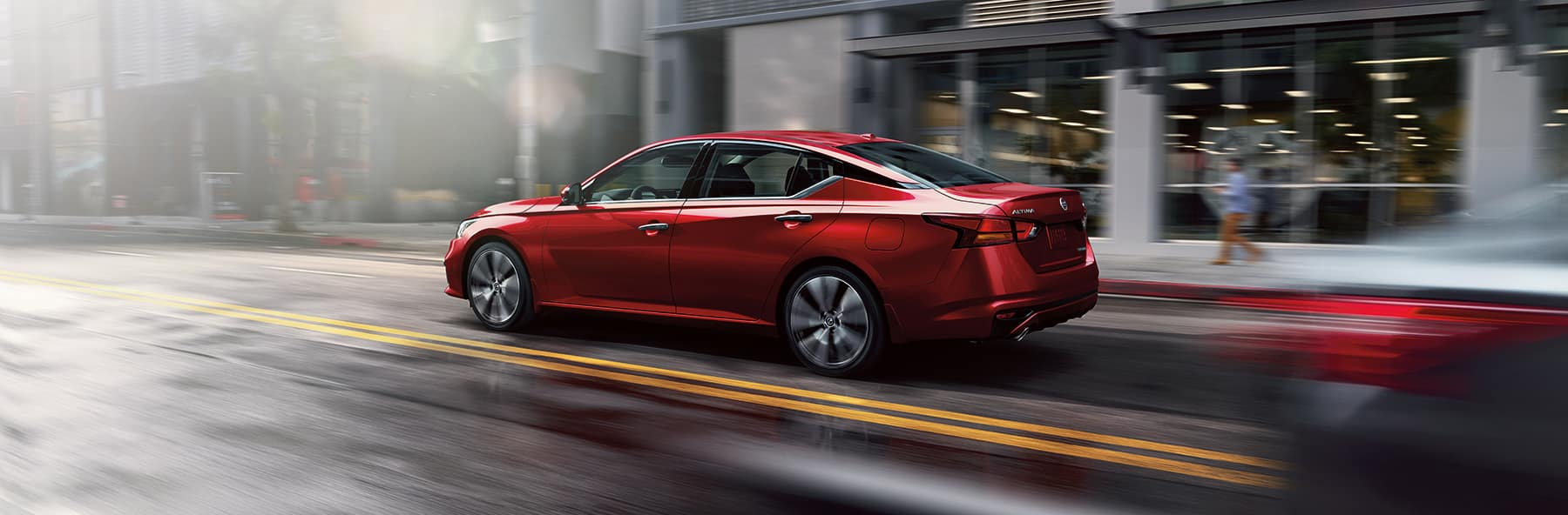 Boch Nissan South is a Nissan Dealer Near Plainville MA | Red 2020 Nissan Altima Driving in City Past Shops