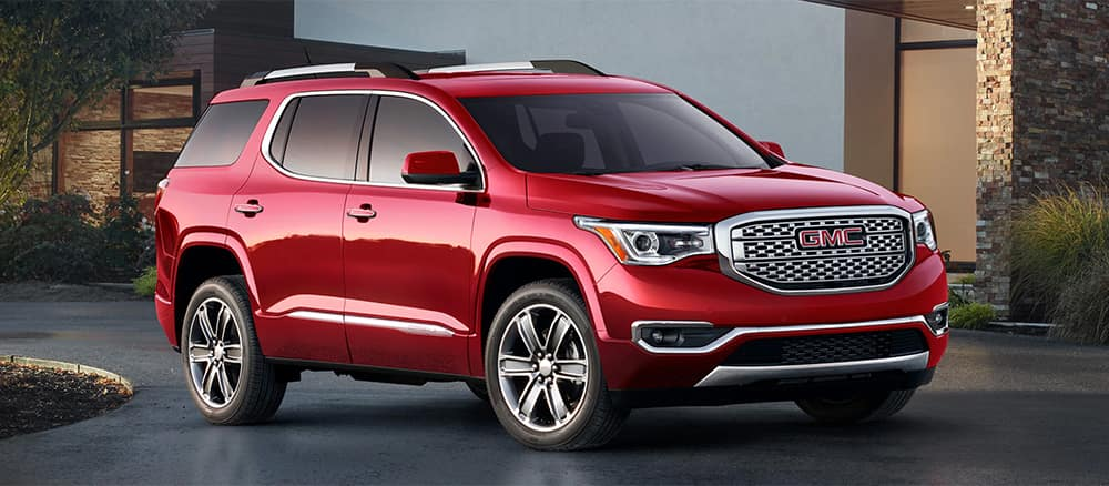 Red GMC Acadia parked in a driveway infront a building