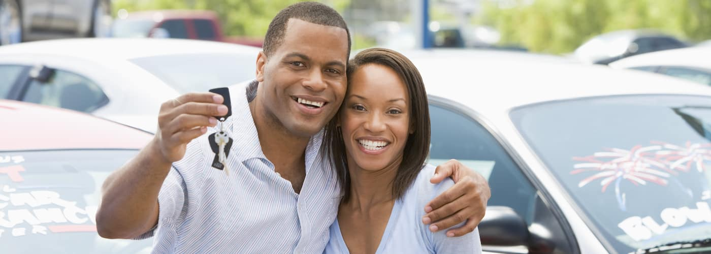 young couple holding up car keys with blurred car inventory in background