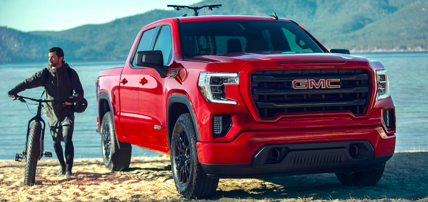 2020 gmc sierra 1500 red exterior parked outside beach with guy walking next to bike