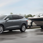 2021 buick enclave towing small speed boat along road