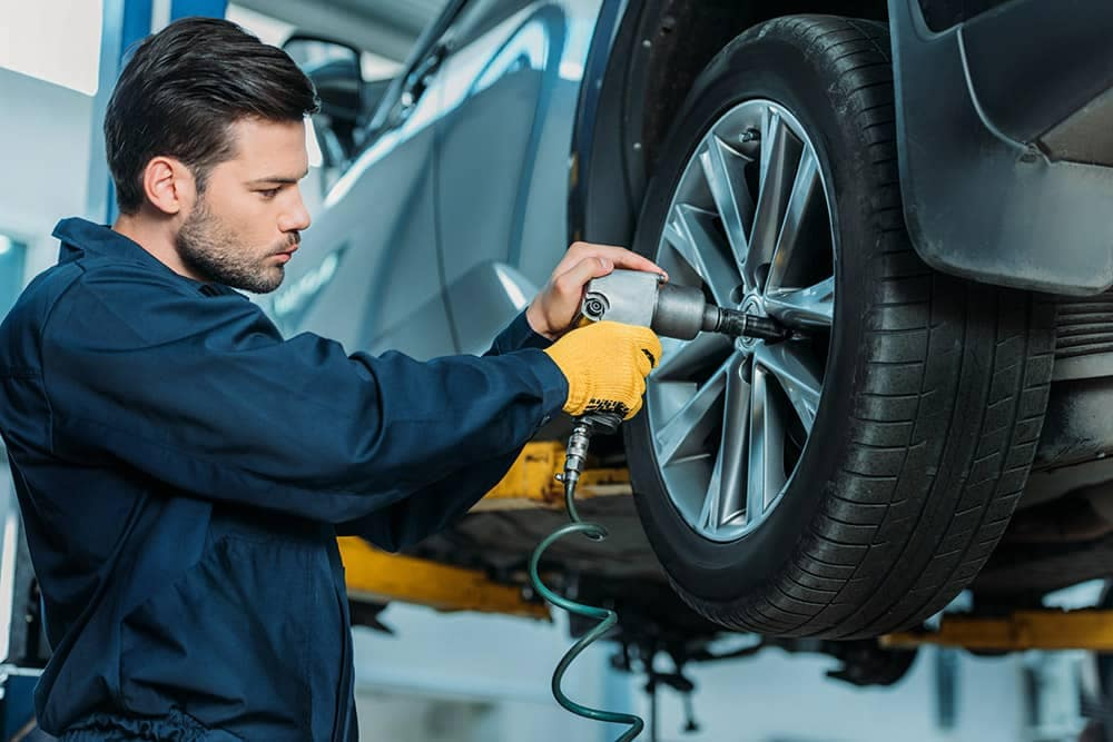 Mechanic removing wheel for tire rotation