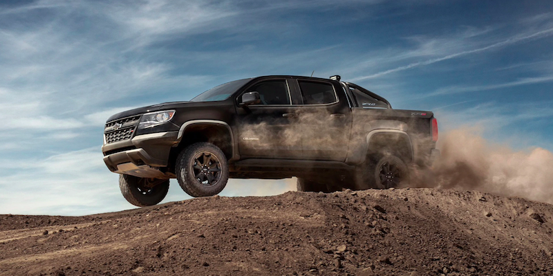 Black Chevy Colorado driving over a dusty hill