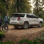 2021 chevy white tahoe parked outside with people and their bikes