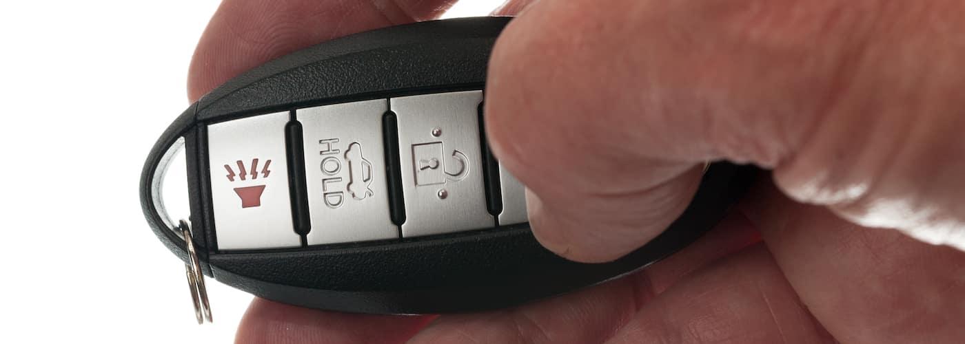 mans thumb on key fob close up