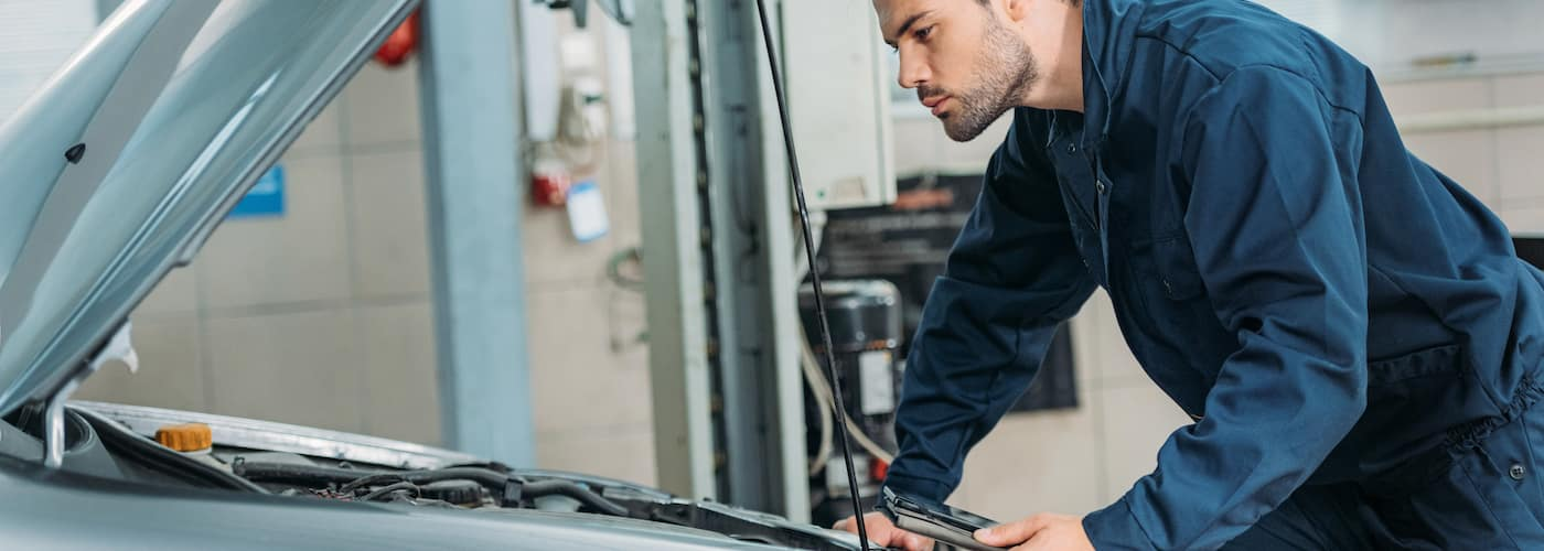 mechanic checking under hood of car