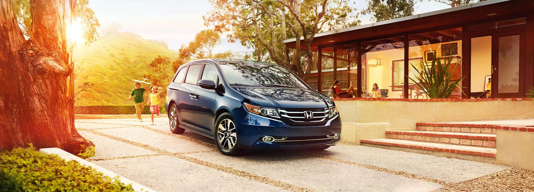 Used Honda Odyssey parked in front of a home while kids play in the driveway