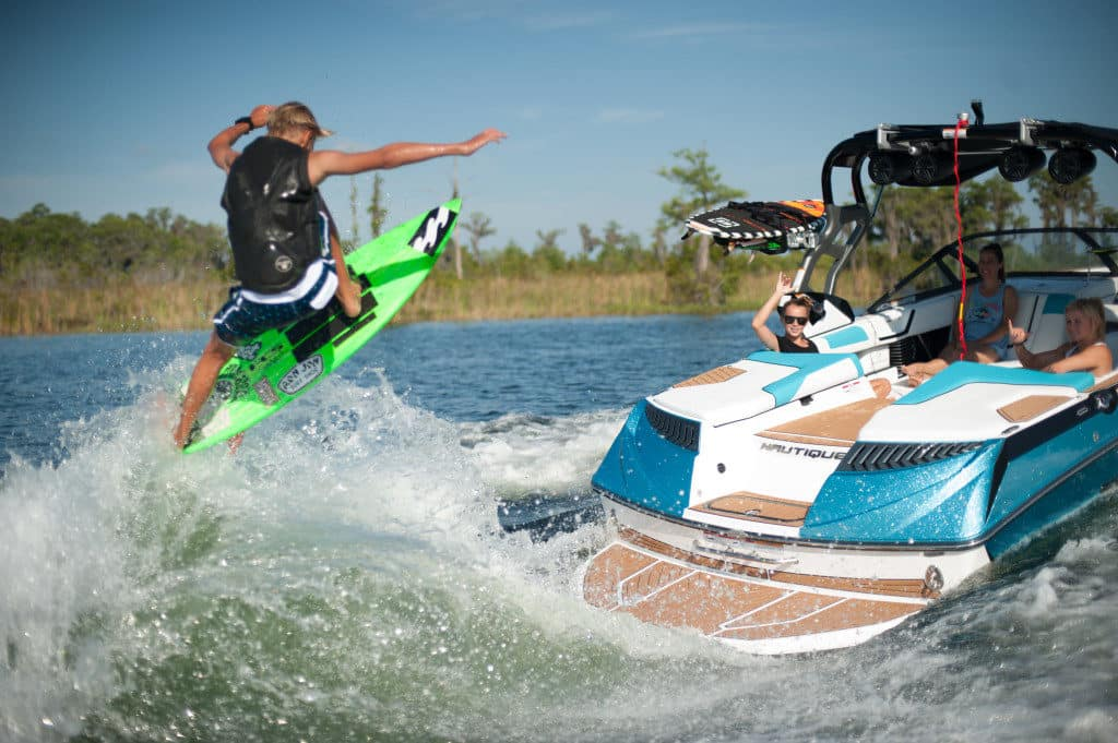 person doing a trick on a wakesurf board behind a boat
