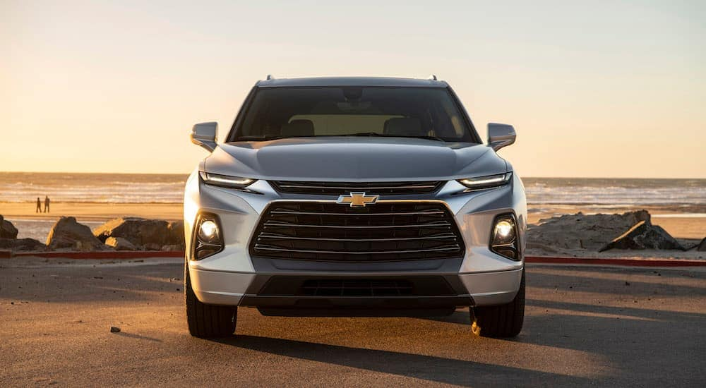 A grey 2019 Chevy Blazer is parked in front of a beach during a sunset.
