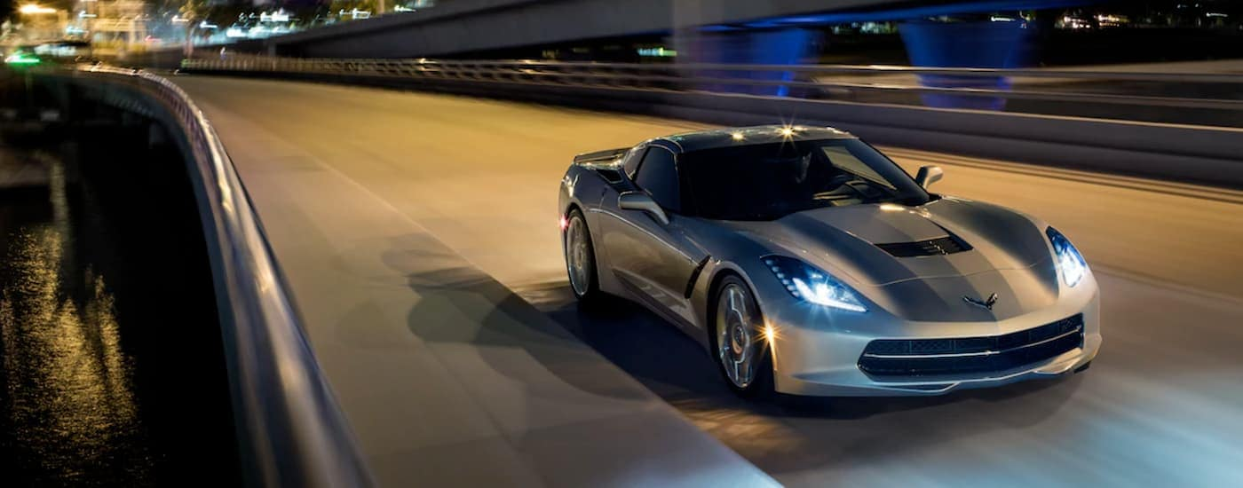 A silver 2019 Chevy Corvette Stingray is driving on a highway at night near Bethlehem, PA.