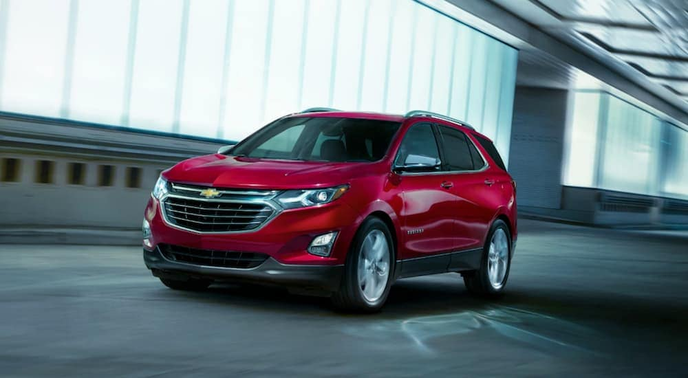A red 2019 Chevy Traverse is driving past lit windows at night in Bethlehem, PA.