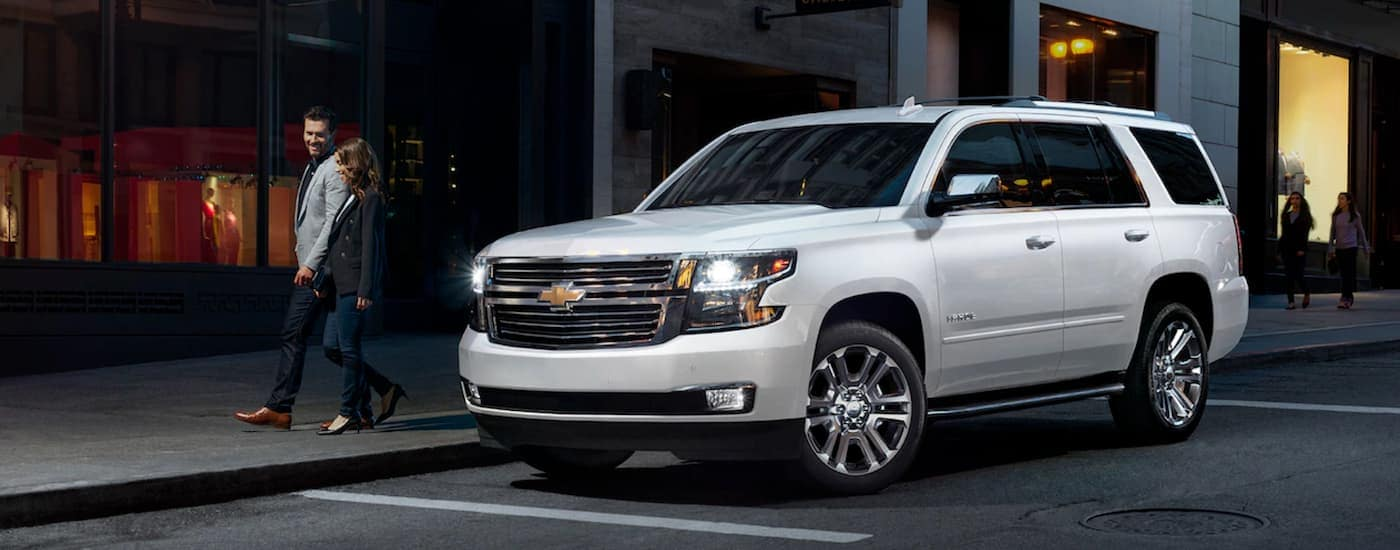 A couple is walking away from their white 2019 Chevy Tahoe downtown at night.