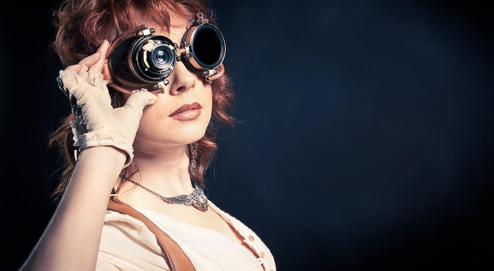 A woman with steampunk glasses is in front of a black background.
