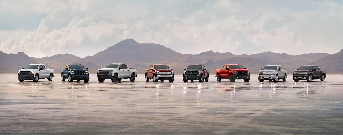 A line of different trim level 2019 Chevy Silverados are in the salt flats.