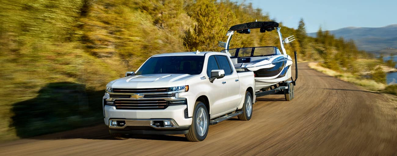 A white 2019 Chevy Silverado is towing a boat.