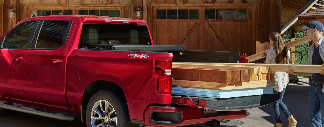 A couple is loading the bed of their red 2019 Chevy Silverado with heavy building supplies.