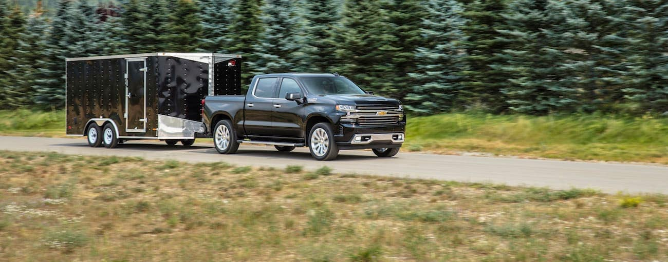 A black 2019 Chevy Silverado, which wins when comparing the 2019 Chevy Silverado vs 2019 Ram 1500, is towing a trailer outside of Bethlehem, PA.