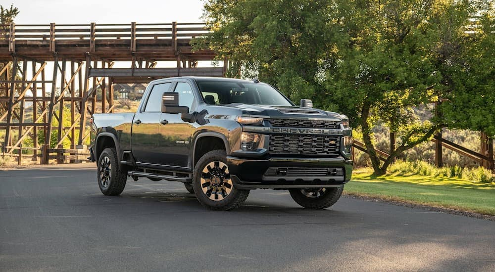 A black 2020 Chevy Silverado 2500HD, popular among Chevy trucks, is parked in front of a wooden bridge near Bethlehem, PA.