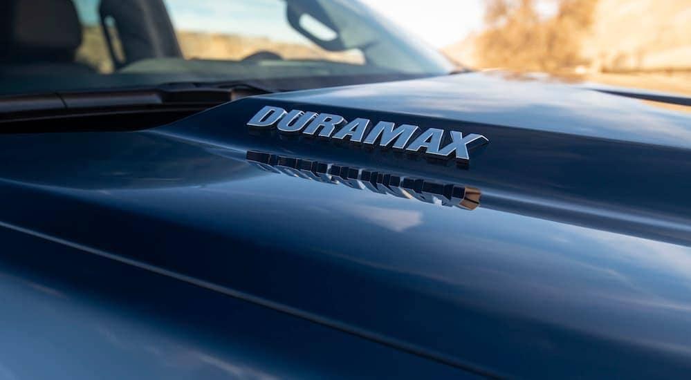 A Duramax logo is on a black hood of a 2020 Chevy Silverado 1500.