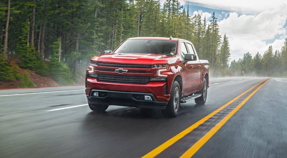 A red 2020 Chevy Silverado 1500 is driving on a wet road.