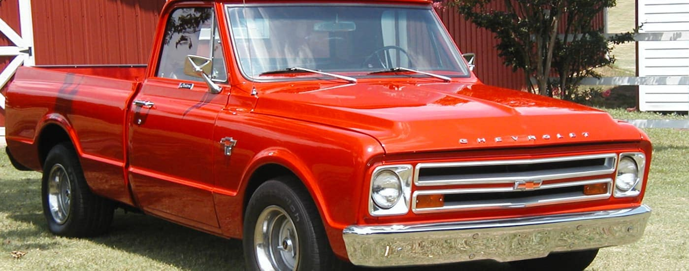 A red 1967 Chevy C/K series is parked in front of a red barn.