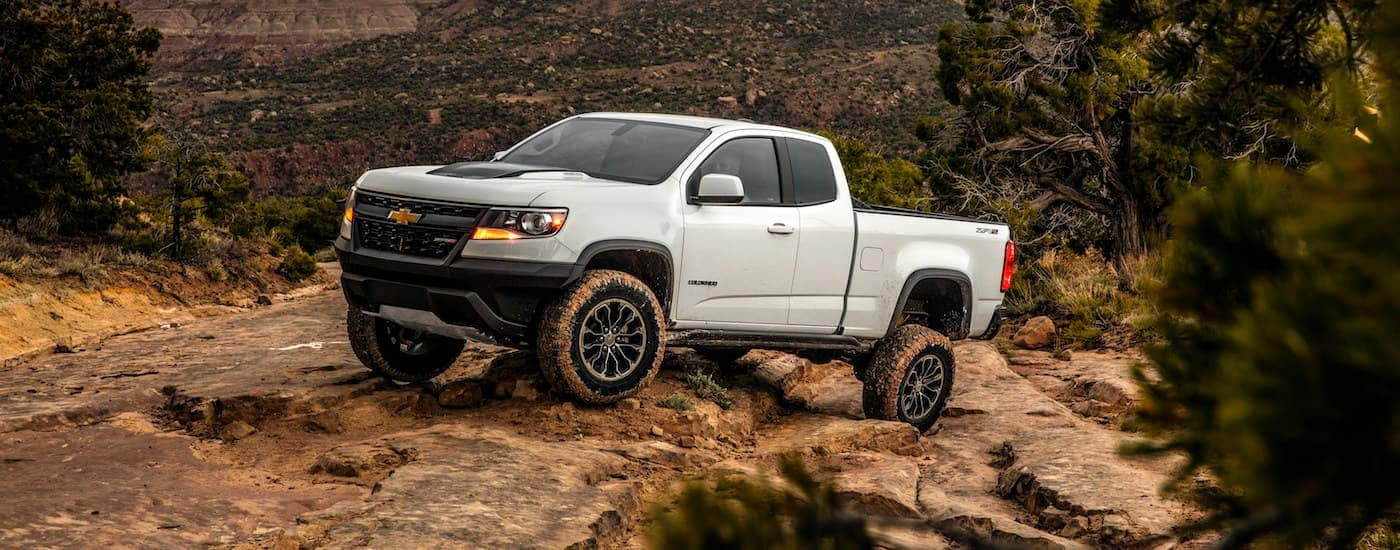A white 2020 Chevy Colorado, which is a popular model among Chevy trucks, is rock crawling up a hill.