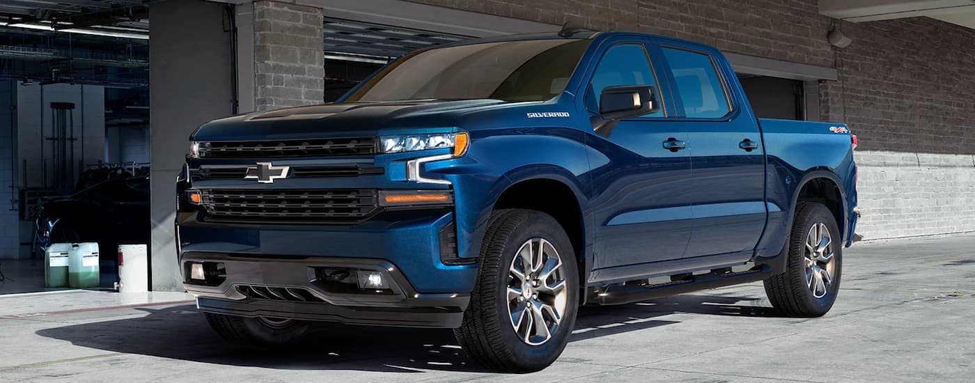 A blue 2020 Chevy Silverado RST is parked in front a garage.