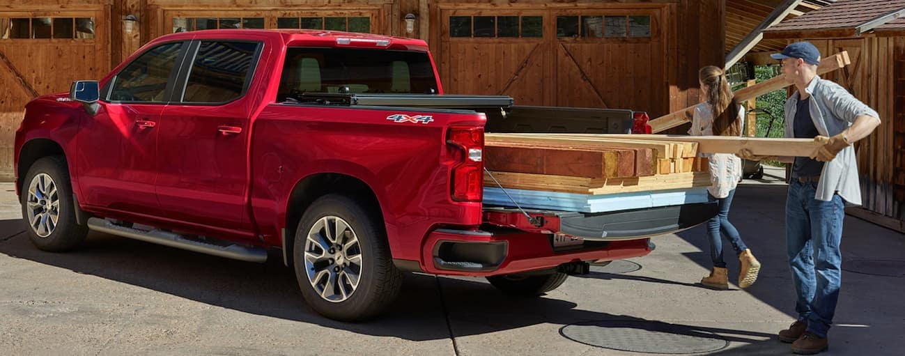 A couple is unloading pieces of wood out of their red 2020 Chevy Silverado 1500.