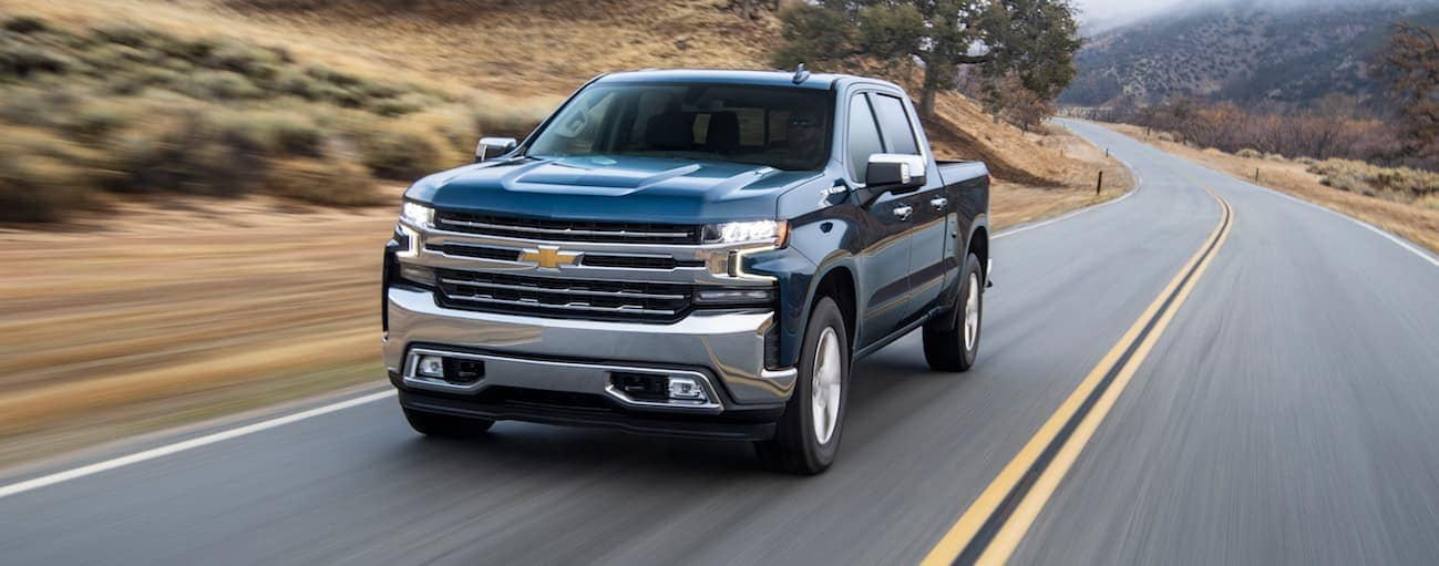 A blue 2020 Chevy Silverado 1500, which wins when comparing the 2020 Chevy Silverado 1500 vs 2020 Ram 1500 in Bethlehem, PA, is driving on a curvy road.